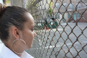 Sara Ferreira looks at the pplayground behind her house--the Oliver Street playground--where her son cannot go to school.