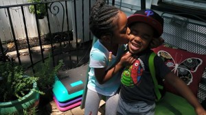 "Lela Barrow, 6, kisses her little brother Richard, 3,  and helps him with his backpack. Because of ""One Newark,"" they can't walk to school together with their grandmother"