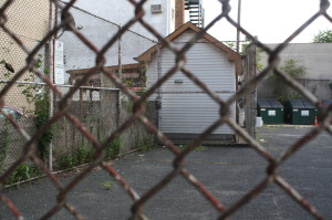 The white shed behind the chain link fence on the Oliver Street in on the Ferreira home property